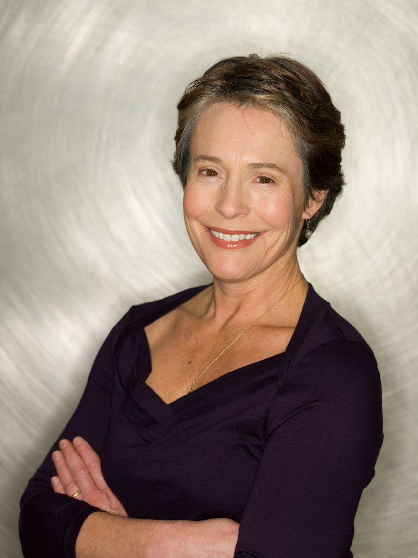Mature woman (50-60 years old) with arms crossed in front of a metal background.