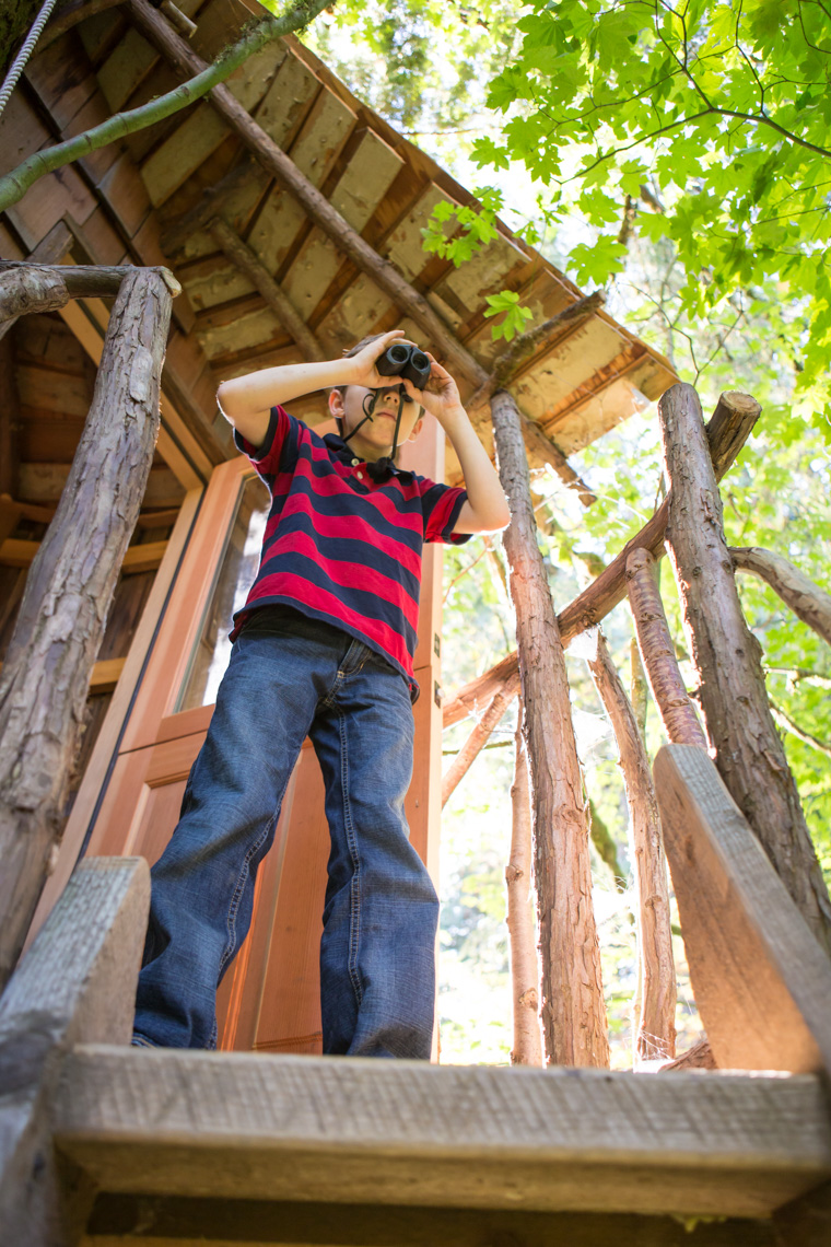 A young boy (8-12 years old) looks out with binoculars from the deck of a treehouse at Treehouse Point, Preston WA, USA.