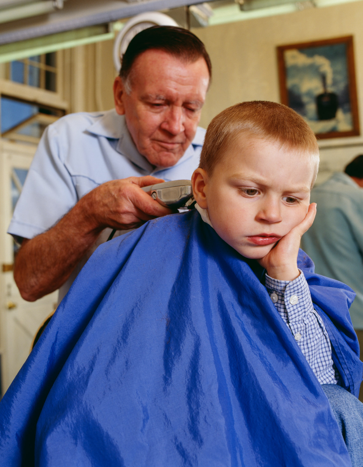 Boy (4-5 years old) having hair cut by male barber.