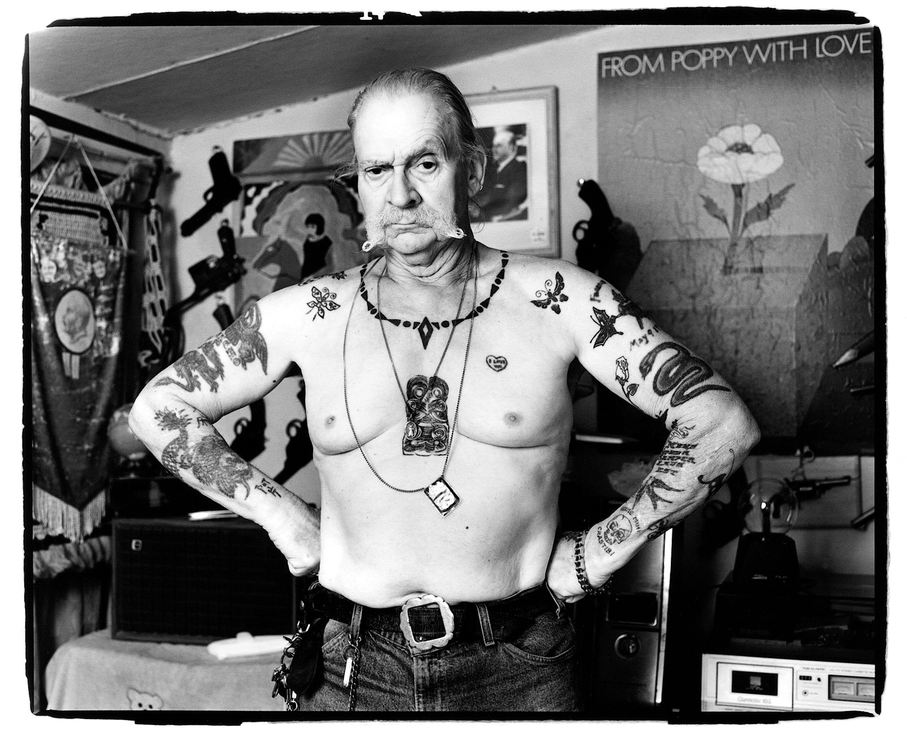 Frank Hillary stands shirtless showing off his tattoos in front of his gun collection in Tucson, AZ.