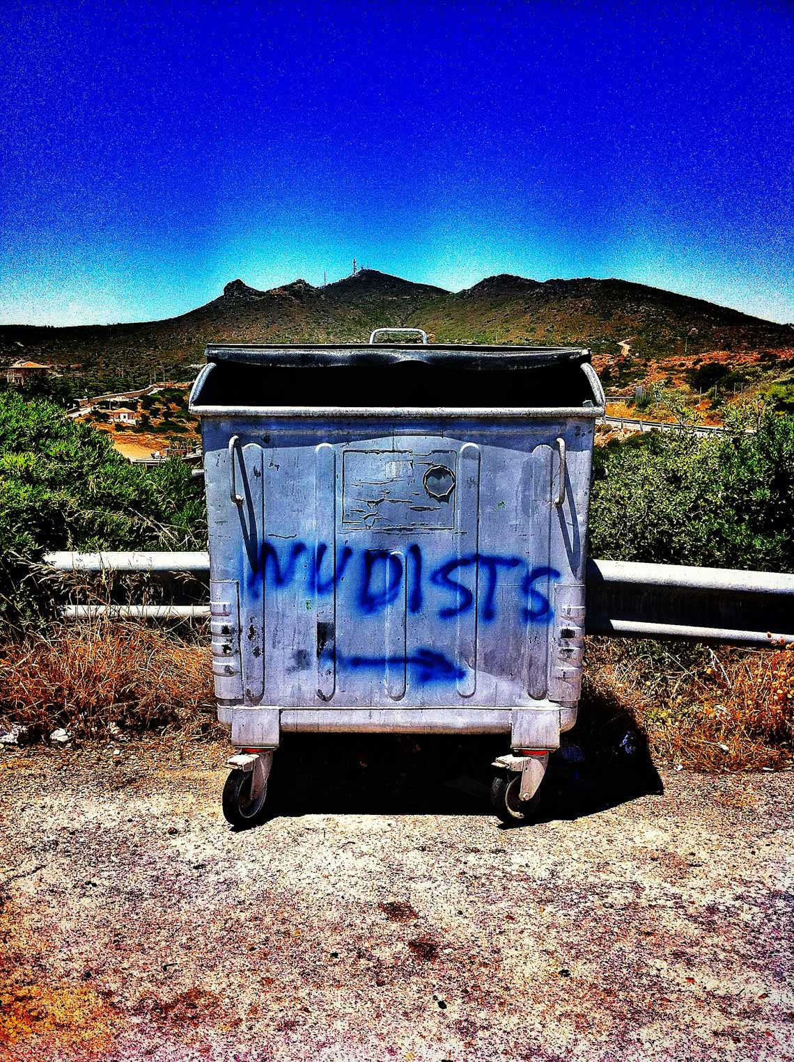 Garbage Dumpster with Nudists Sign Painted on It.