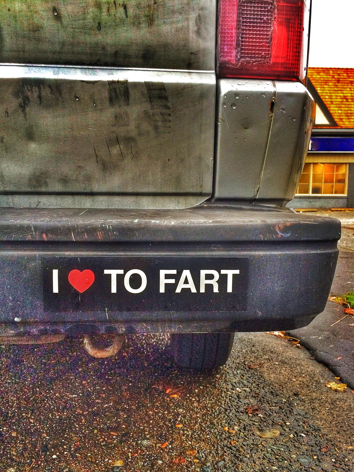 """I love to fart"" bumber sticker on the back of a dirty car."