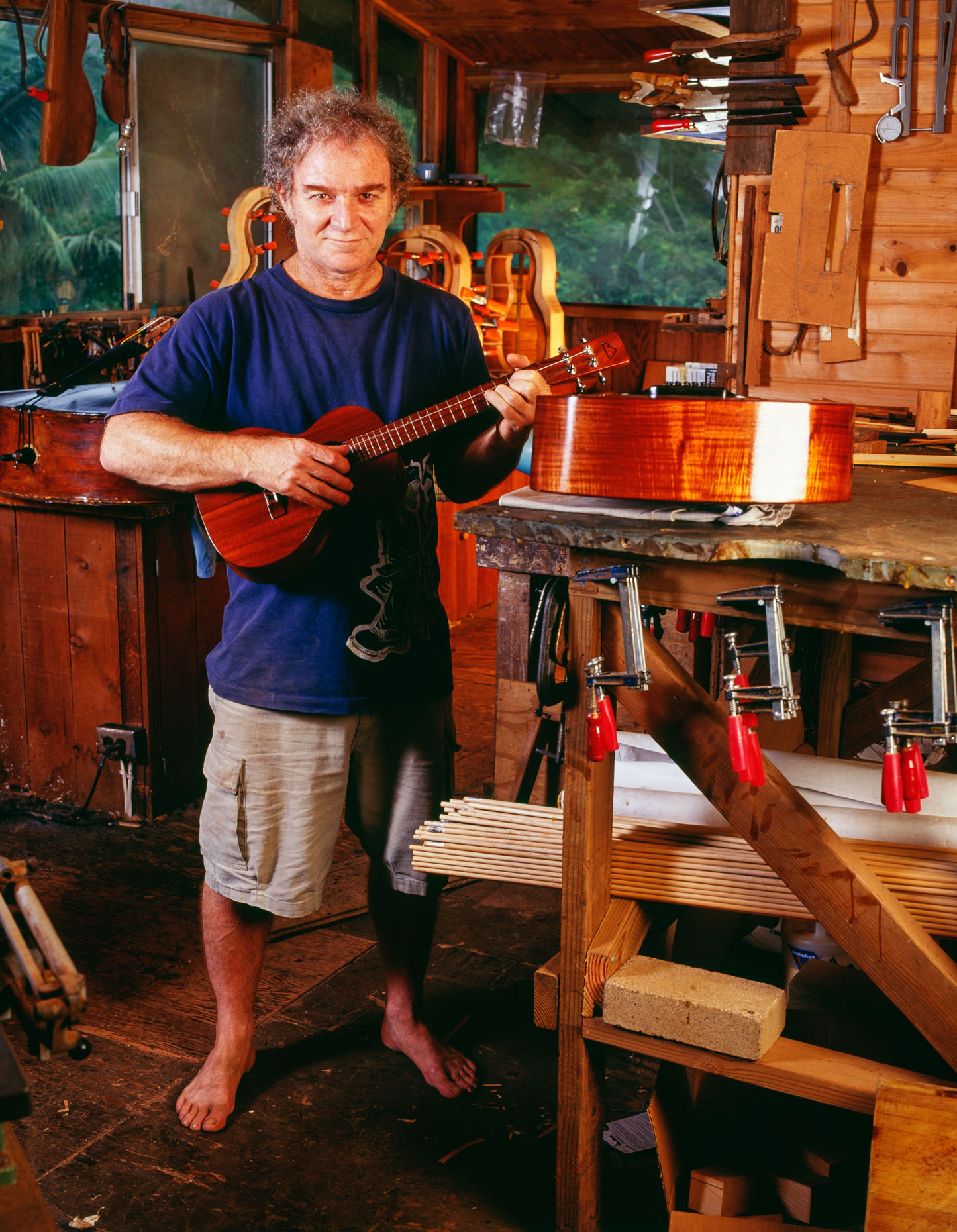Luthier (Mature man) playing ukelele in his workshop, portrait