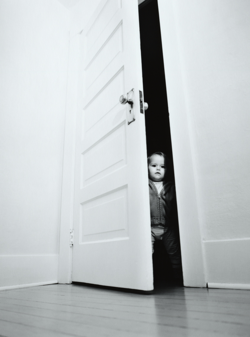 Toddler opens a door (black and white).