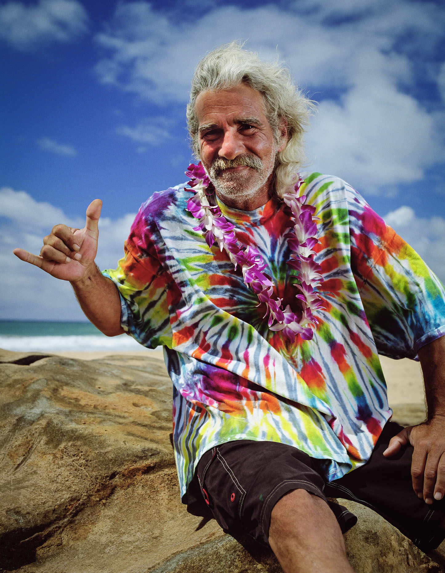 Man in Tie-Dye shirt and lei, gives shaka sign while at the beach near Kapaa Kauai, HI.