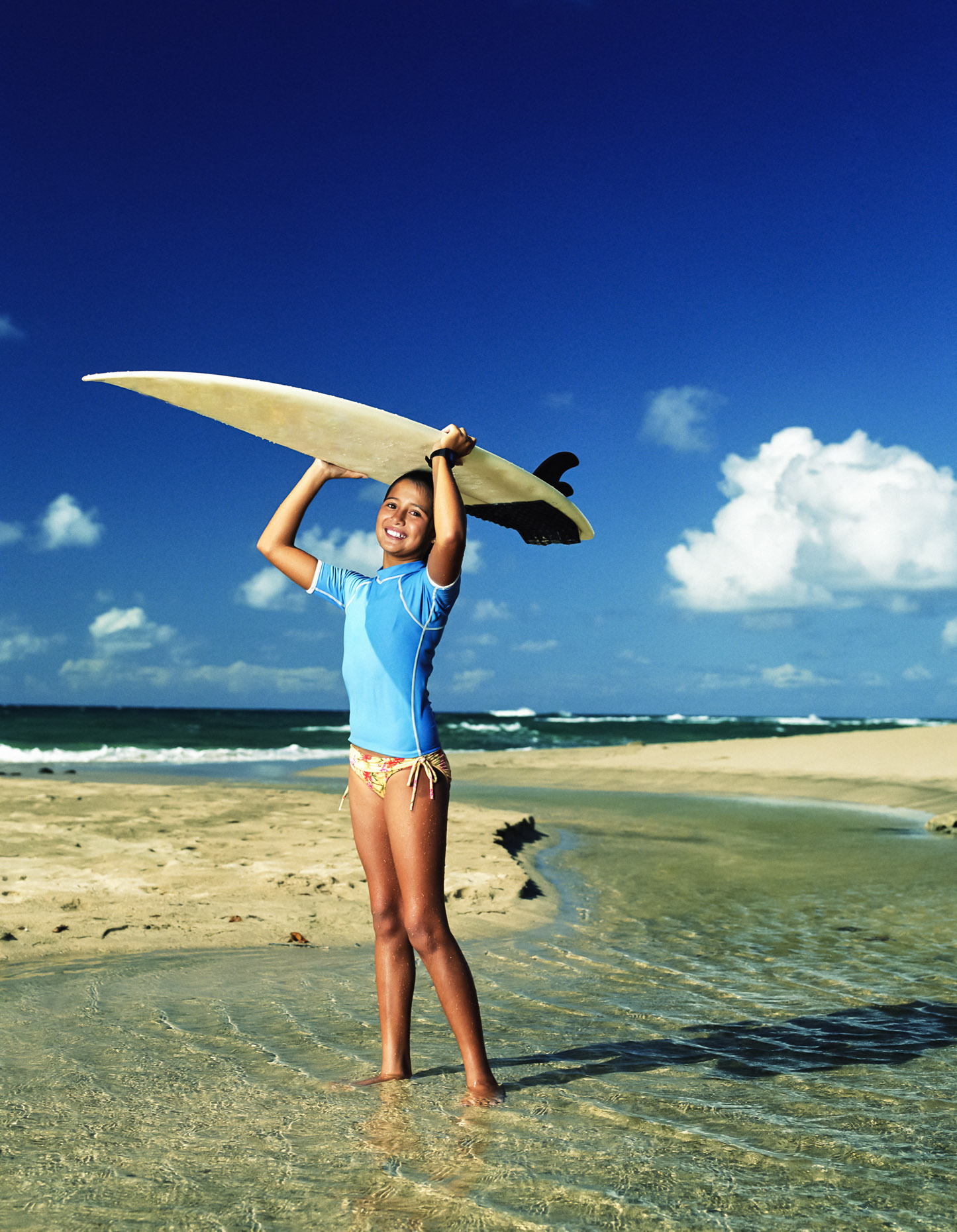 Young girl (8-14 years old) holds a Surfboard over her head near Hanalei, Kauai, HI.