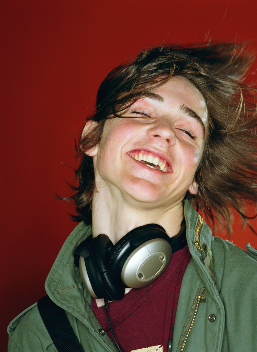 Teenage boy (14-16) tossing head back, smiling, headphones around neck